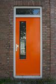 Orange Door on Brick House — Stock Photo