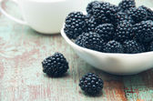 Blackberries in a bowl on wooden table — Stock Photo