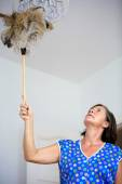 Woman cleaning with feather dusters — Stock Photo