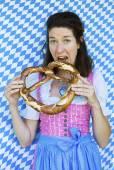 Woman in dirndl with pretzel — Stock Photo