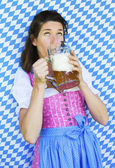 Woman in dirndl drinking beer — Stock Photo