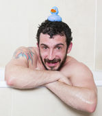 Man in bathtub with rubber duck — Stock Photo