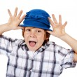 Blond boy with blue hat making faces — Stock Photo #54467205