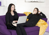 Two woman sitting on couch with a laptop — Stock Photo