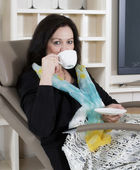 Woman in armchair with cup — Stockfoto
