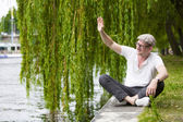 Man sitting by the water — Stock Photo