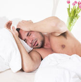 Man in bed with a headache — Stock Photo