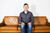Man itting on couch — Stockfoto