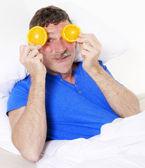 Man in bed with oranges — Foto de Stock
