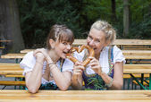Two woman in dirndl with pretzel — Stock Photo