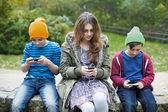 Three kids with phones — Stock Photo