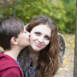 Boy kissing teenage girl on her cheek — Stock Photo #55676935