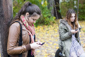 Two girls with phones  — Stockfoto