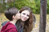 Boy kissing teenage girl on her cheek — Stock Photo