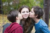 Two boys kissing a teenage girl — Stock Photo