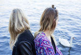 Two women by the waterfront and a swan — Стоковое фото