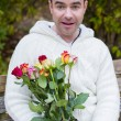 Man sitting on a bench with roses — Stock Photo #57316399