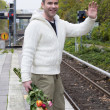 Man waiting at train station with flowers — Stock Photo #57317161