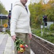 Man waiting at train station with flowers — Stock Photo #57317175