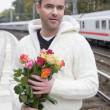 Man waiting at train station with flowers — Stock Photo #57317529