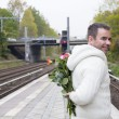 Man waiting at train station with flowers — Stock Photo #57317531