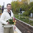 Man waiting at train station with flowers — Stock Photo #57317561
