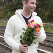 Man waiting at train station with flowers — Stock Photo #57317767