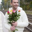 Man waiting at train station with flowers — Stock Photo #57317875