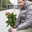 Man waiting at train station with flowers — Stock Photo #57317945