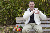 Man on bench shaping heart with his hands — Stock Photo