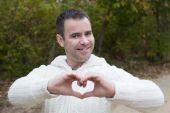 Man outside shaping heart with his hands — Stock Photo