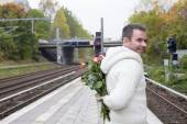 Man waiting at train station with flowers — 图库照片