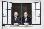 Two businessmen looking out of a window — Stock Photo