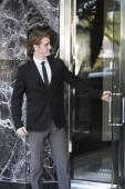 Man in suit opens a door — Stock Photo