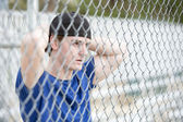 Young man behind a fence — Stock Photo