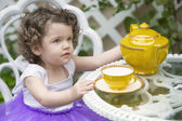 Toddler sitting in garden with teapot — Stock Photo