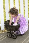 Little girl in pink dress with a pram — Stock Photo