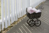 Vintage stroller in front of white fence — Stock Photo