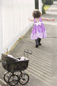 Little girl in pink dress chasing soap bubbles — Stock Photo
