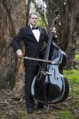 Man playing the double bass in park — Stock Photo