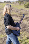 Man with guitar on a field — Stock Photo