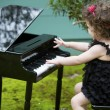 Little girl playing on toy piano — Stock Photo #62489337