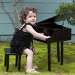 Little girl playing on toy piano — Stock Photo #62489377