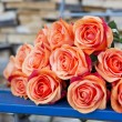 Orange roses on a blue rustic chair — Stock Photo #74745487