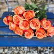 Orange roses on a blue rustic chair — Stock Photo #74745519