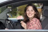 Young woman sitting in a car and holding a flower — Stock Photo