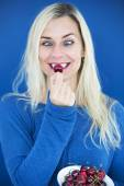 Blond cross-eyed woman eating a cherry — Stock Photo