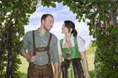 Bavarian couple standing underneath a tree — Stock Photo