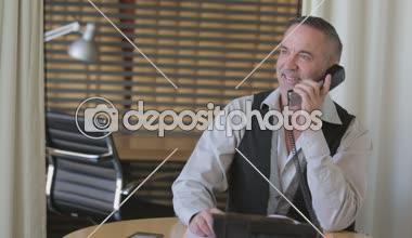 Apuesto hombre de negocios hablando por teléfono en su oficina — Vídeo de Stock