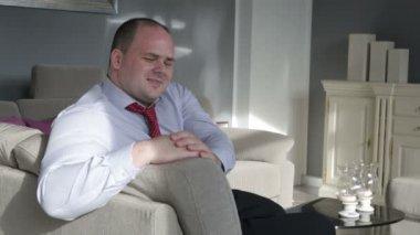 Geschäftsmann, sitzen im Wohnzimmer auf couch und ist an der Kamera flirten — Stockvideo
